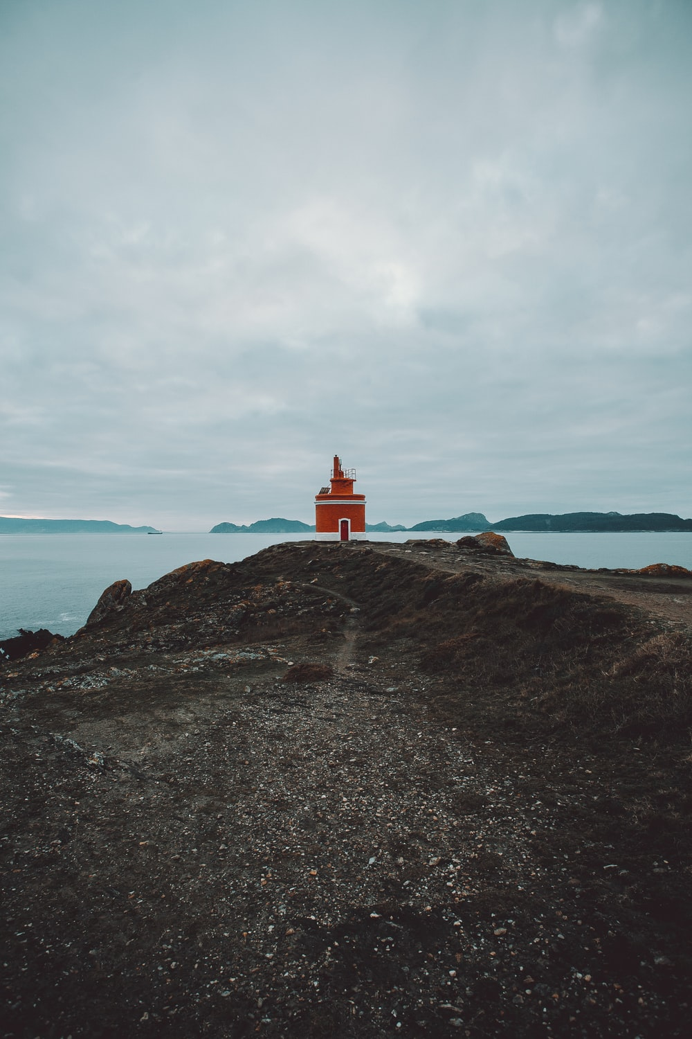 red lighthouse on island during day