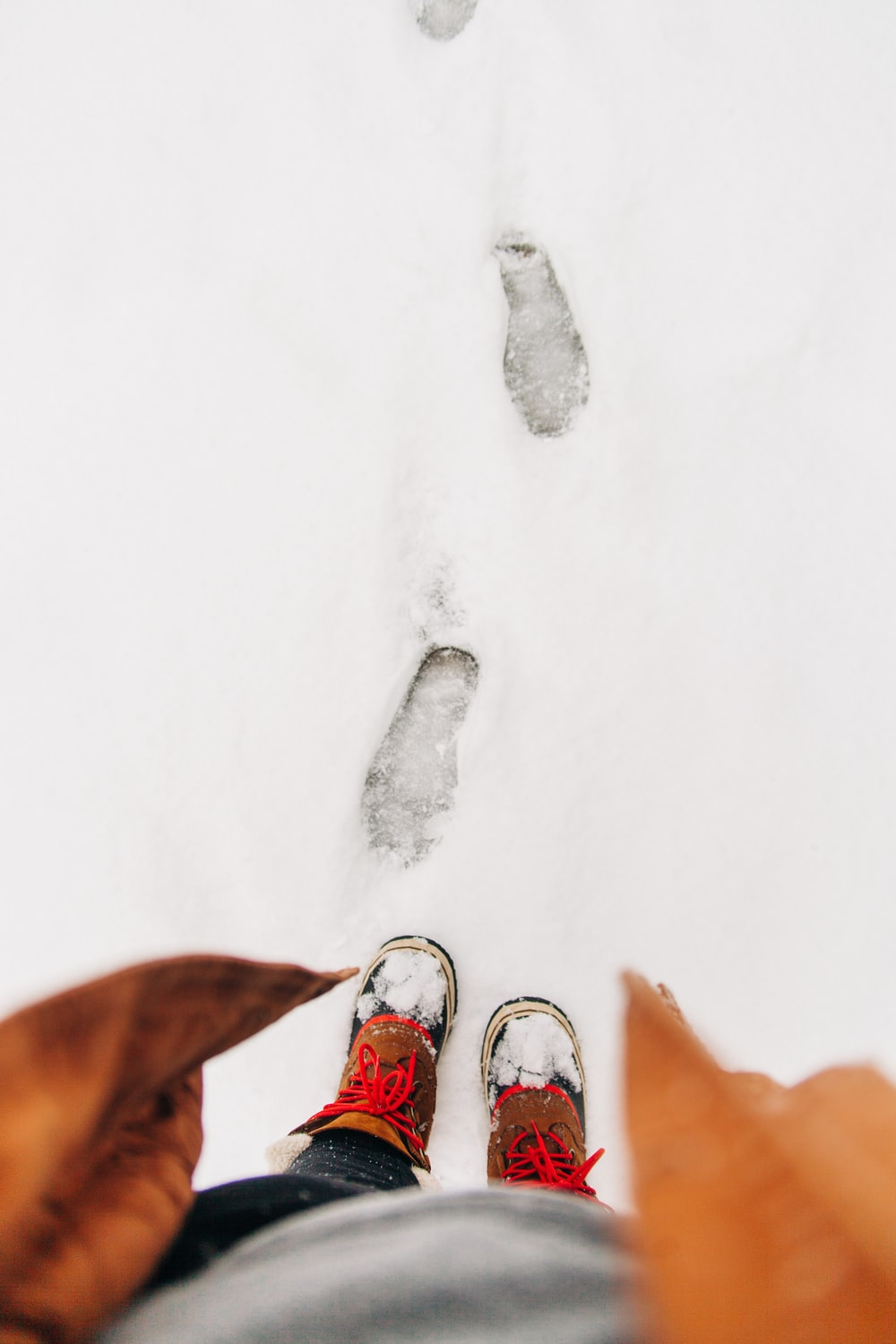 person standing on snowfield with footprints