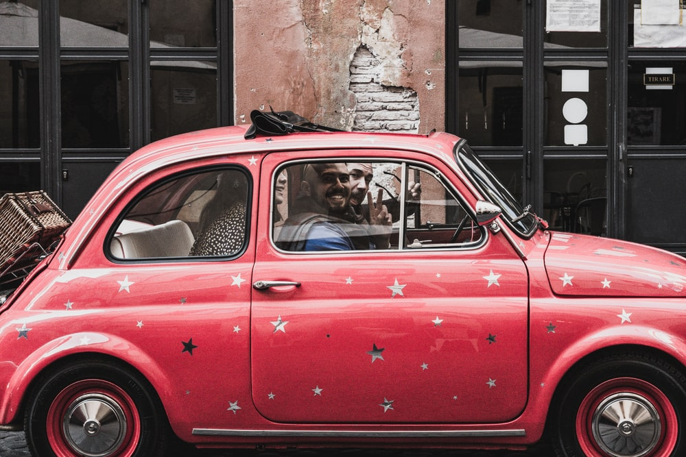man riding on the red Volkswagen beetle