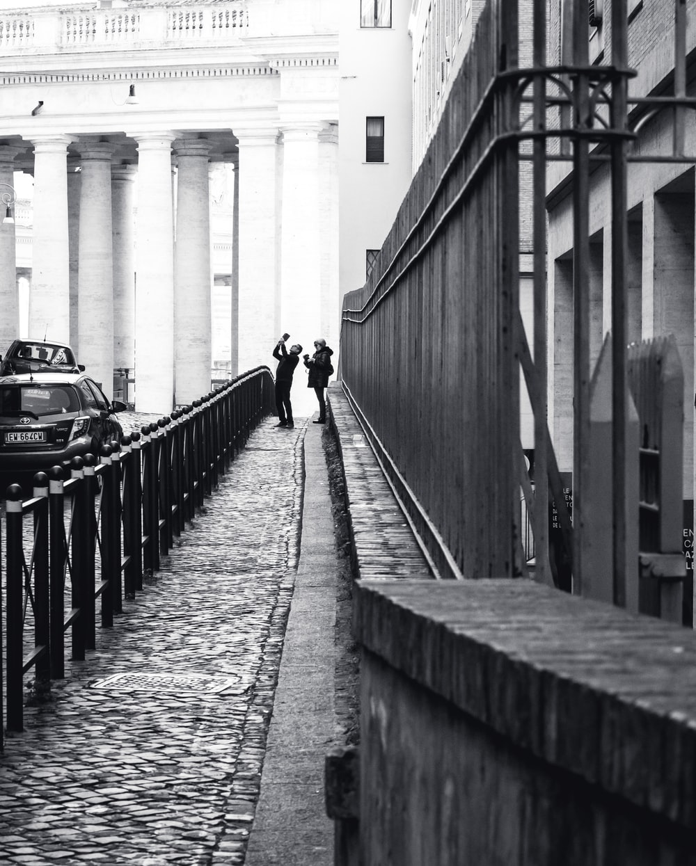 grayscale photography of two people standing near railings beside building