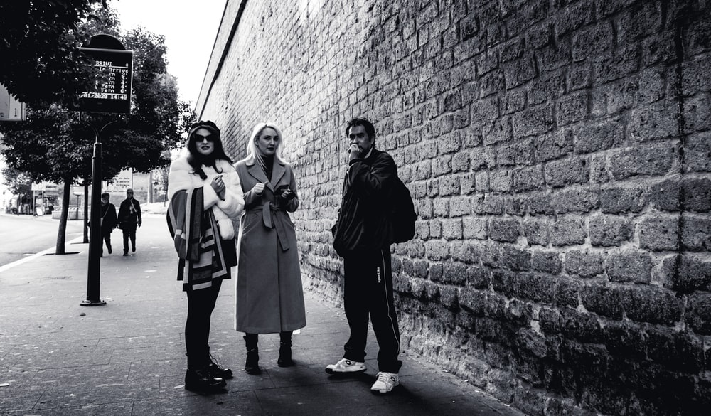 grayscale photography of three people standing on pathway near building