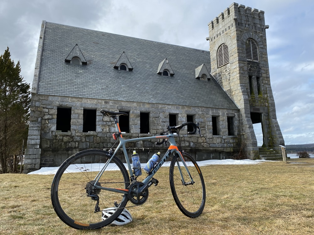 road bike parked on grass near building with tower during day
