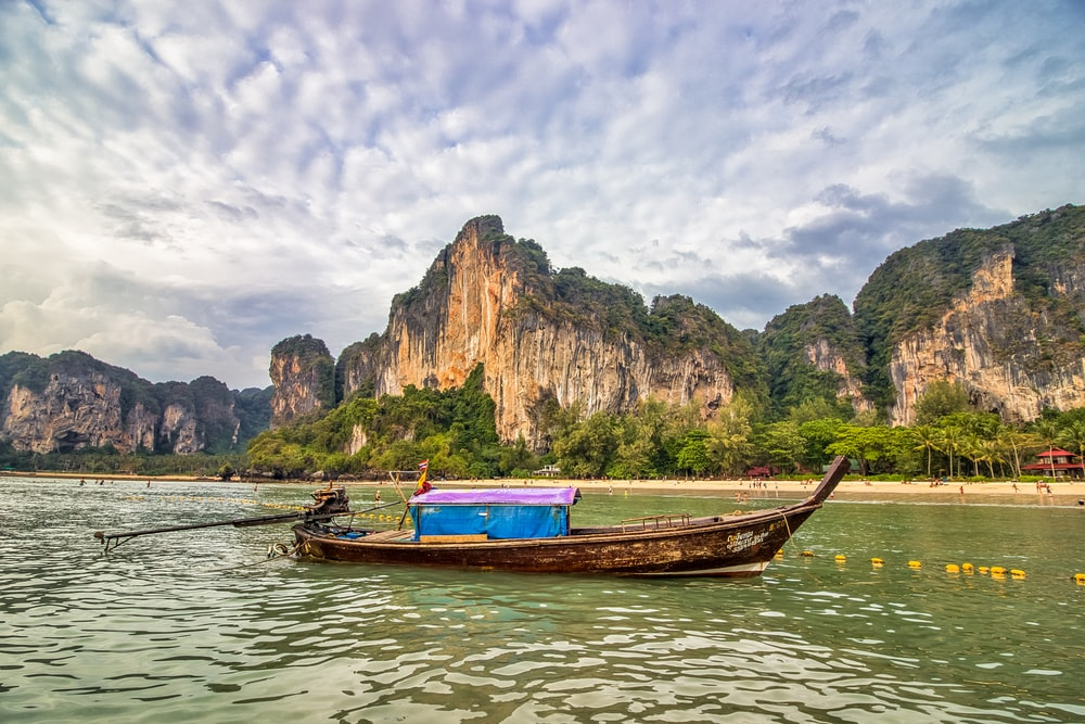 boat on water near mountains at daytime