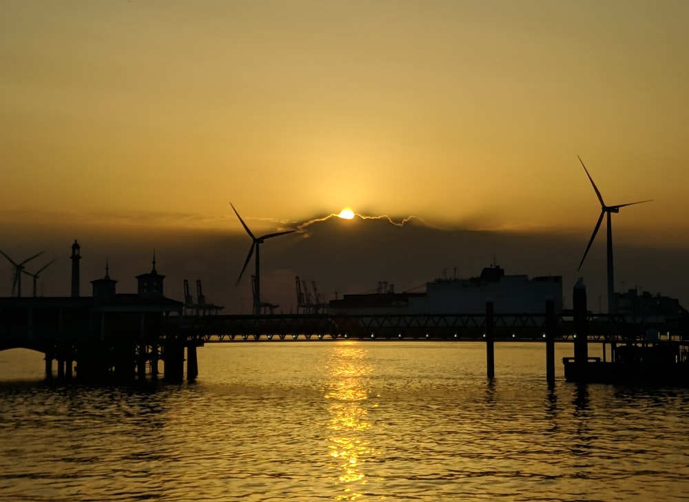 silhouette photography of windmills by the sea during golden hour