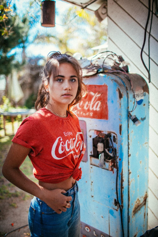 woman in red Coca-Cola t-shirt standing beside Coca-Cola fridge