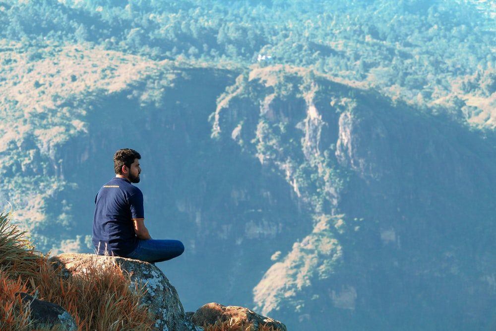 man sitting on the mountain cliff photograph