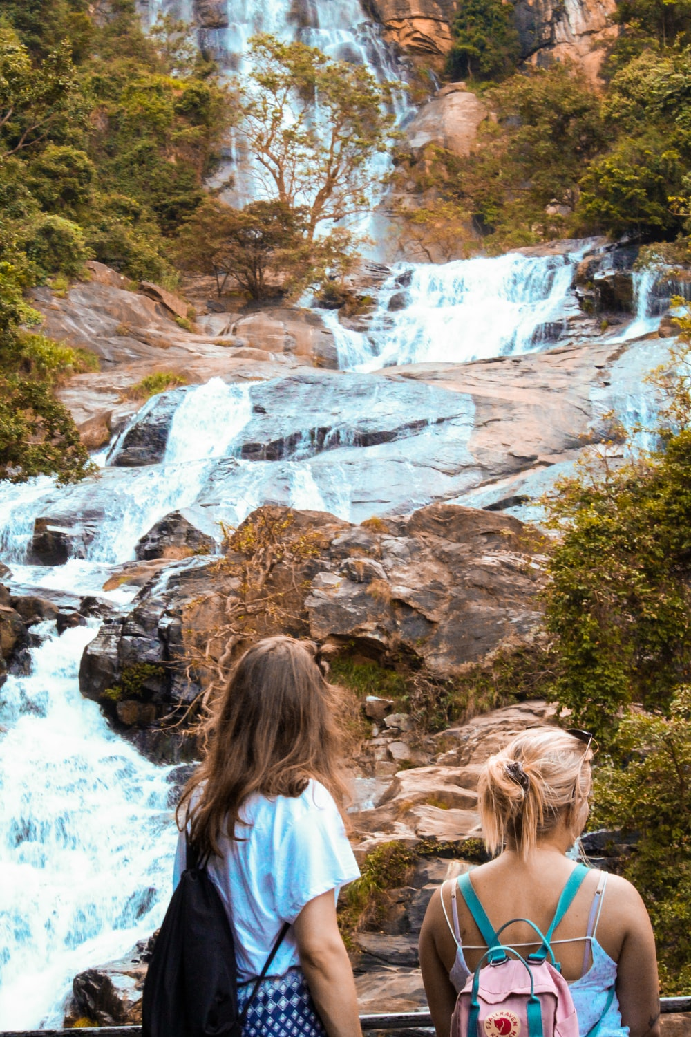 two women looking at a flowing multi-tier waterfall