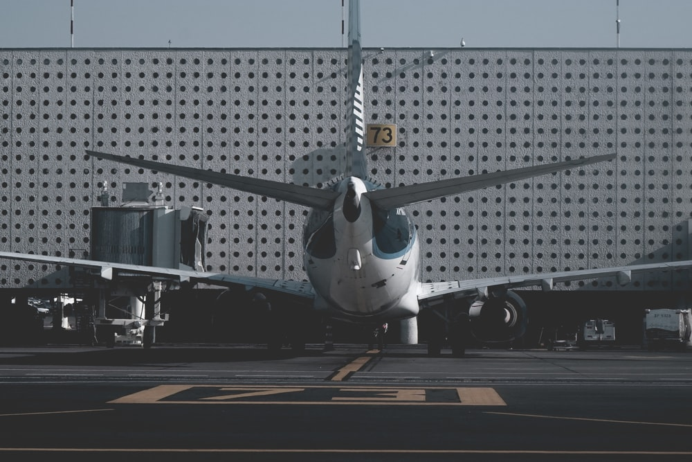 white and blue airliner parked on port