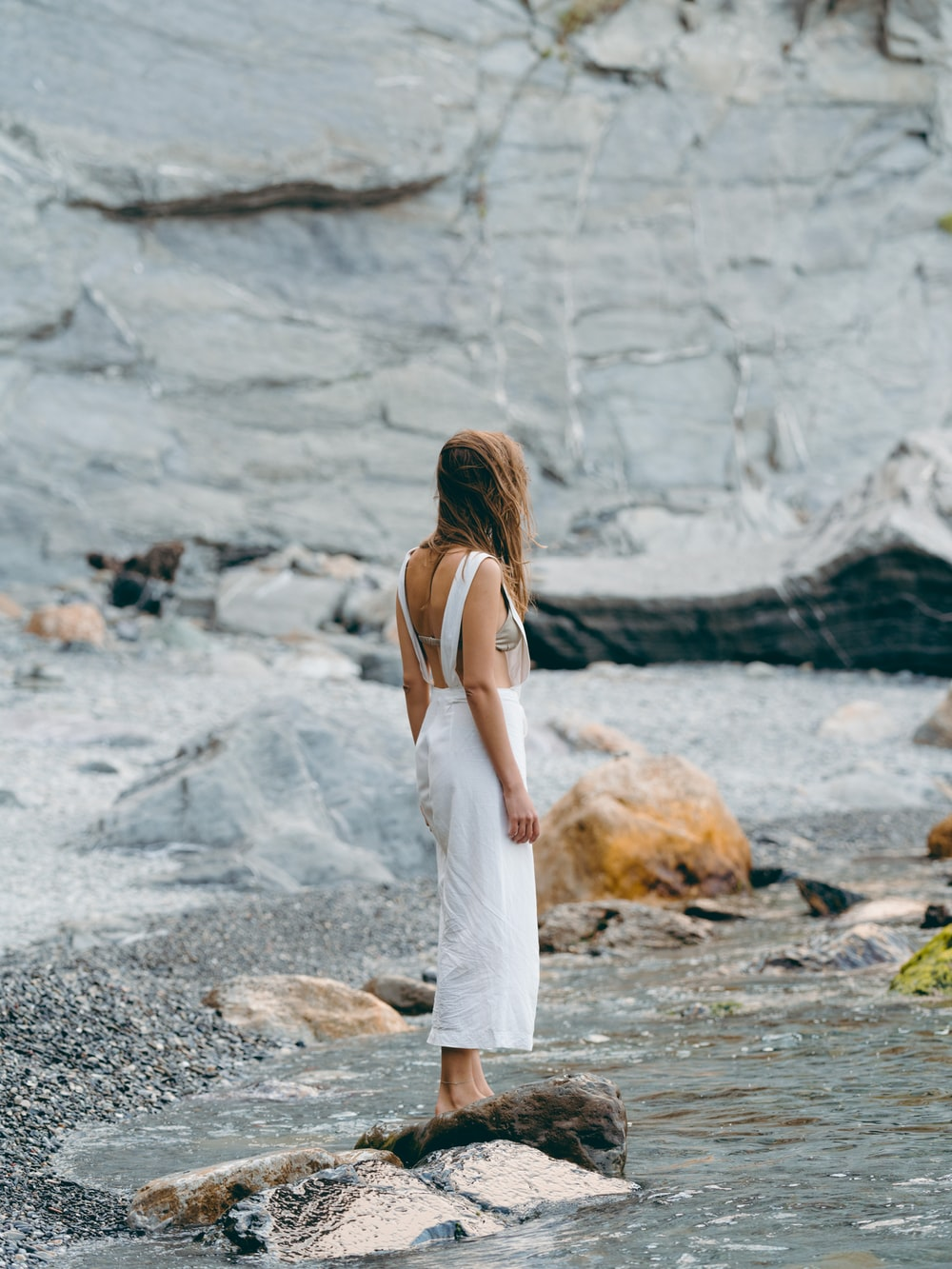 woman wearing white dress standing on the stone near the body of water