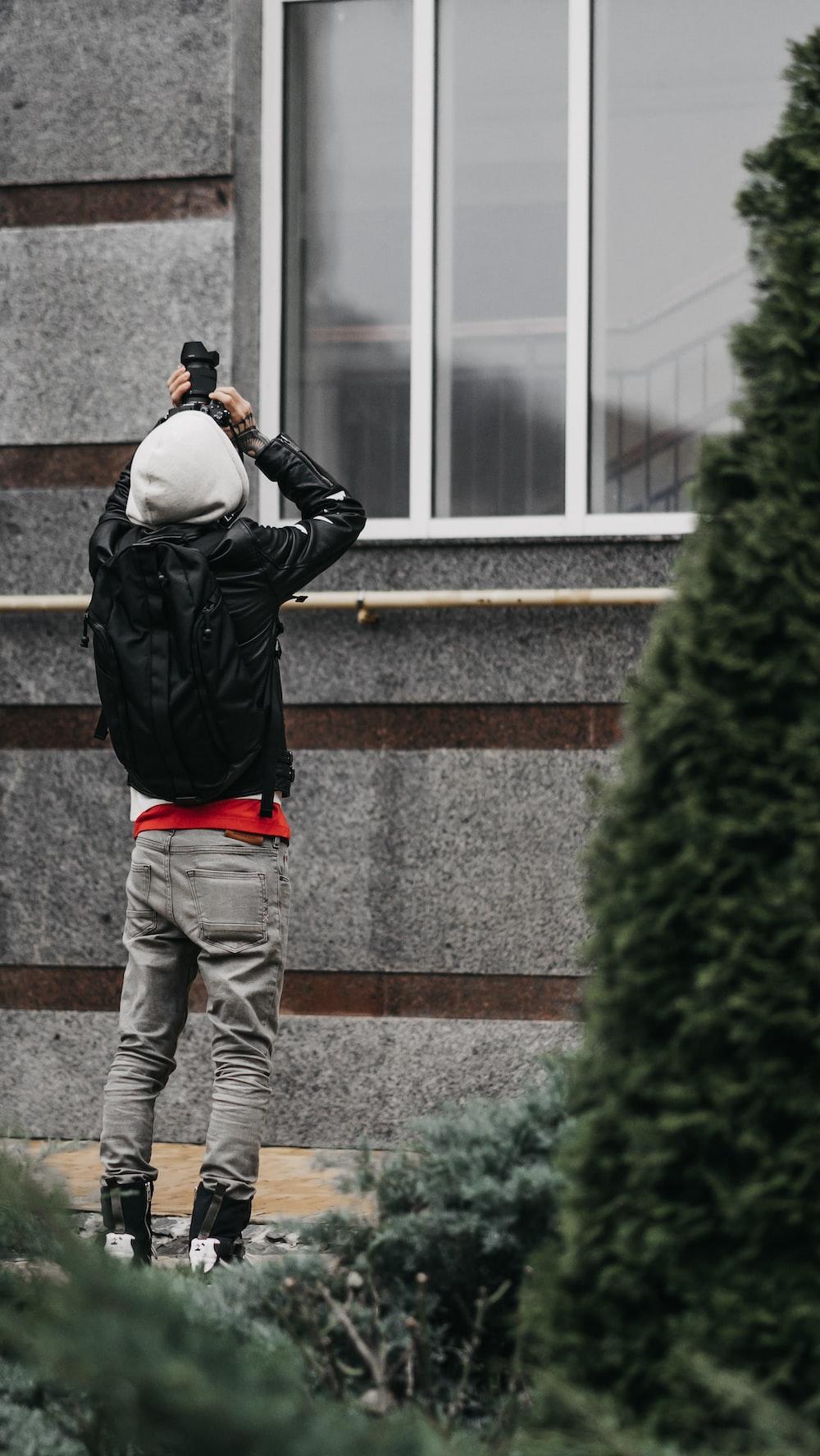 man wearing black leather jacket standing near the window