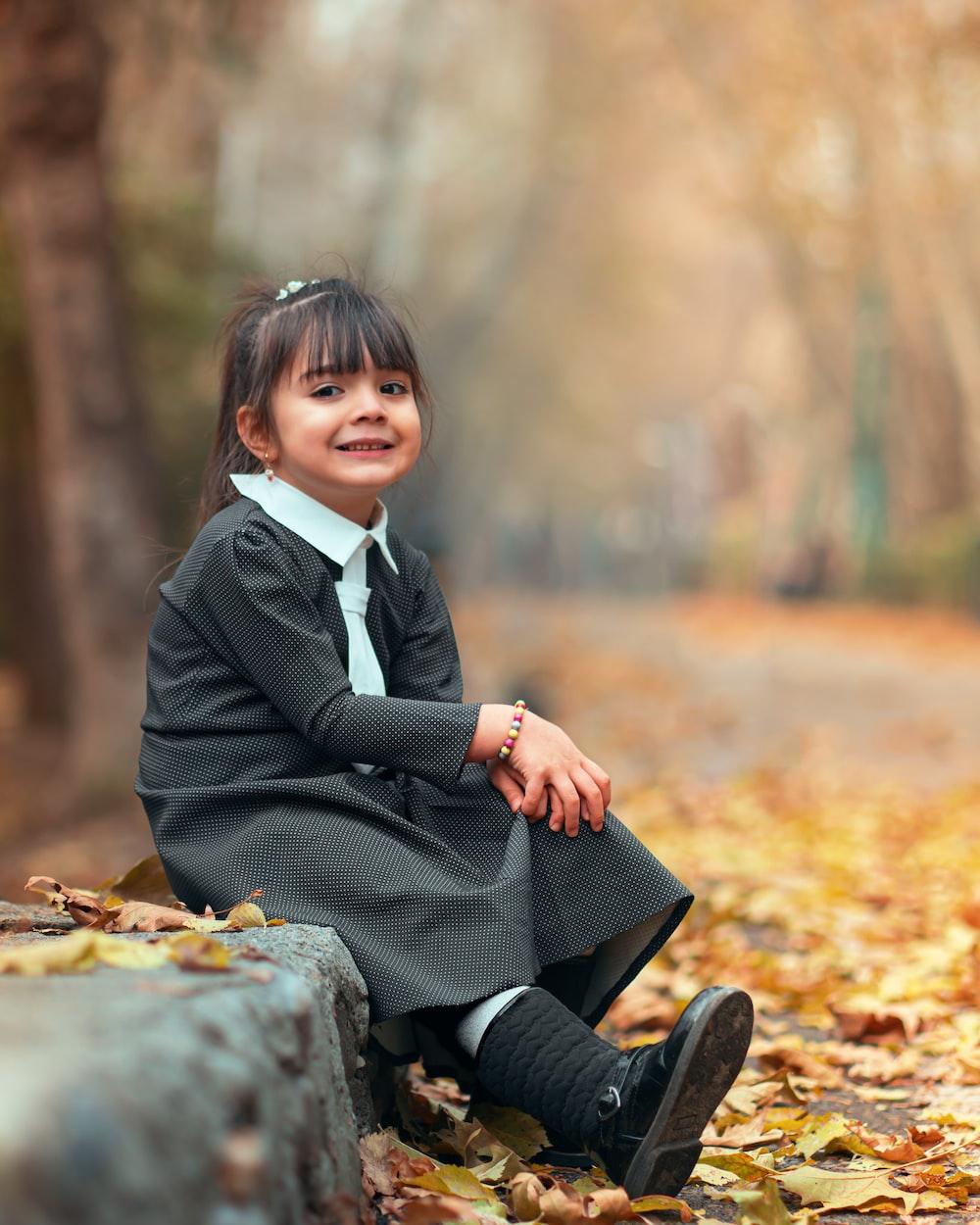 smiling girl sitting beside road