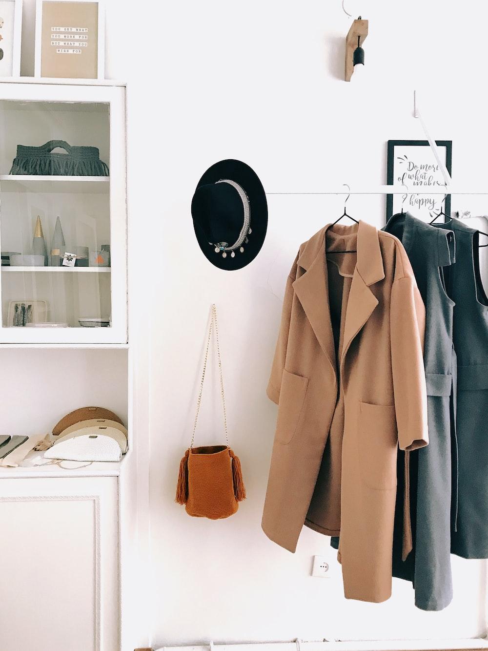 brown coat hanging beside the crossbody bag