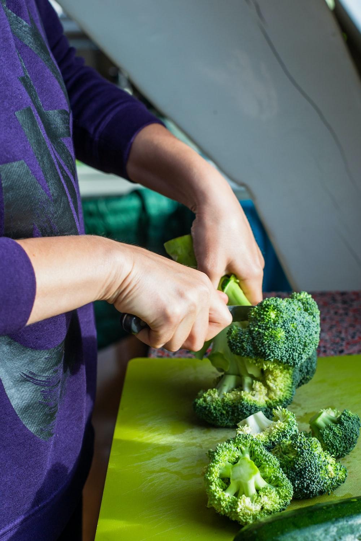 person slicing green broccoli
