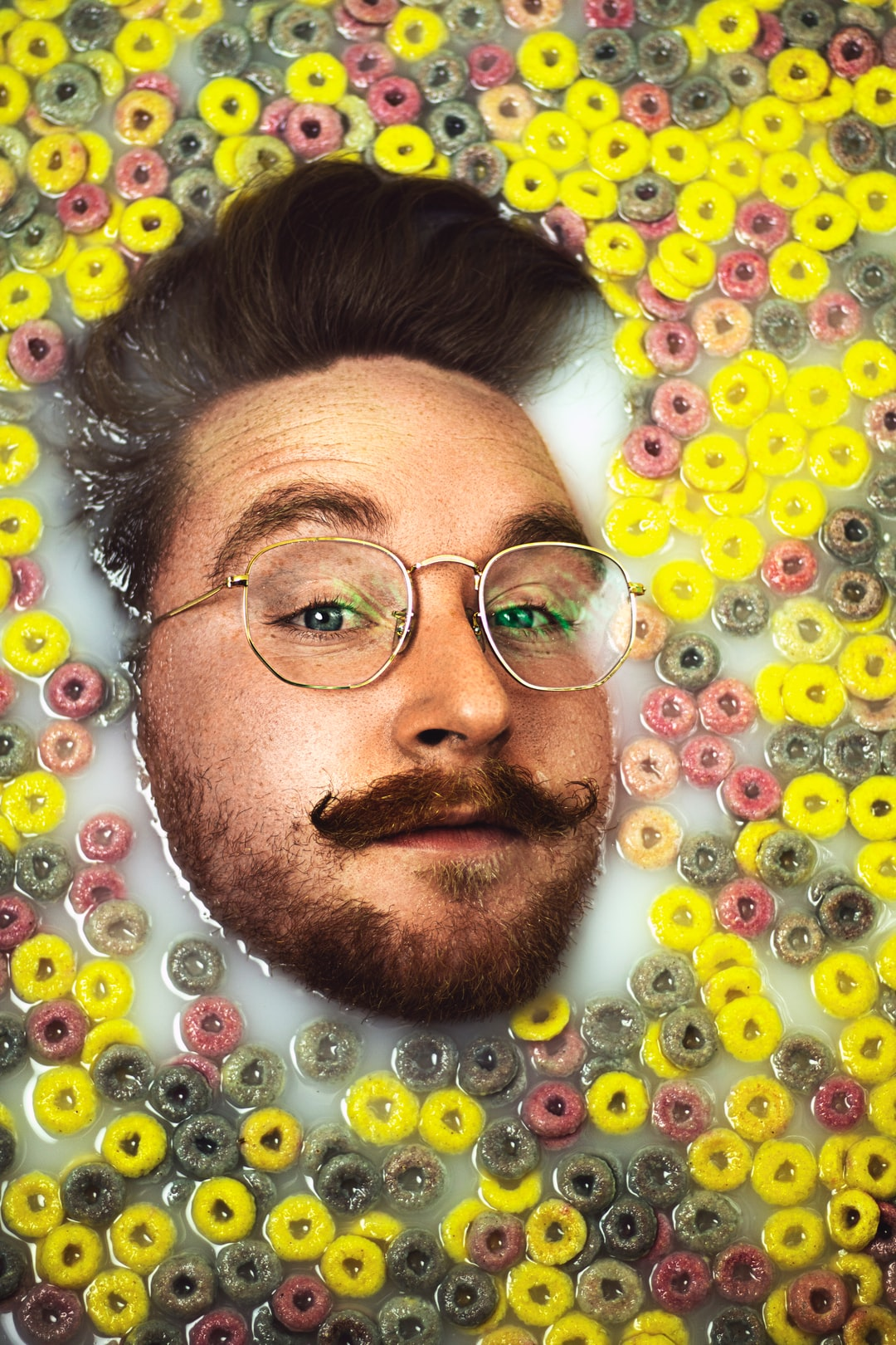 Man with vintage wireframe glasses in fruit loop cereal bath, with ginger beard, quiff and moustache