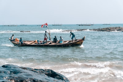 people riding boat at the ocean during day ghana teams background