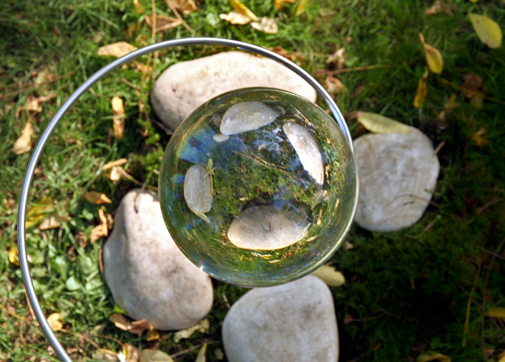clear ball reflecting rocks and grass