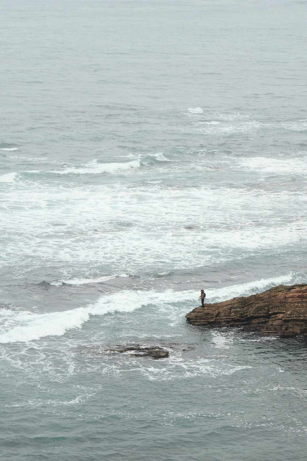 person standing on coastal rock during daytime