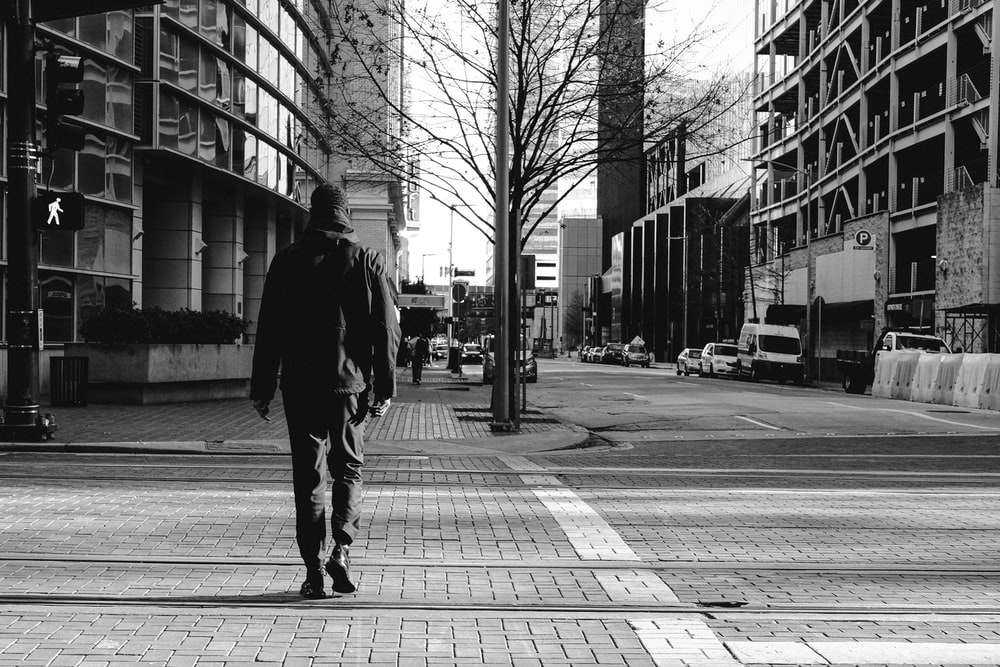 man walking on sidewalk during daytime