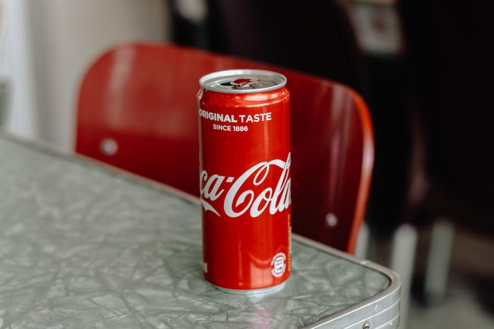 Coca-Cola original taste soda can on edge of gray table