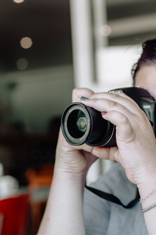 person wearing gray shirt taking photo using black Nikon DSLR camera
