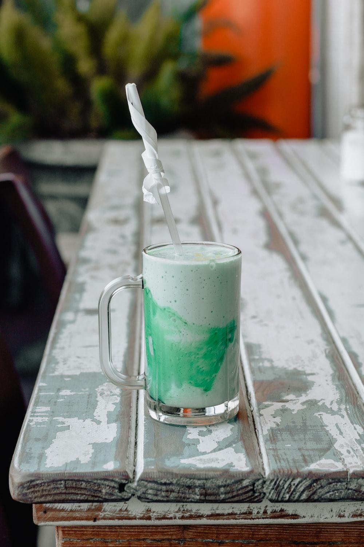 milk tea in clear glass mug on edge of white wooden table