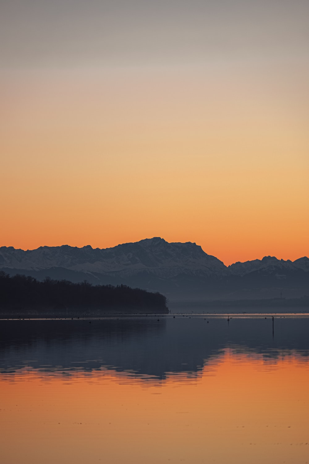 silhouette photography of a mountain and body of water during golden hour