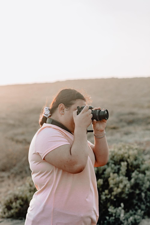 woman wearing pink t-shirt standing while taking photo