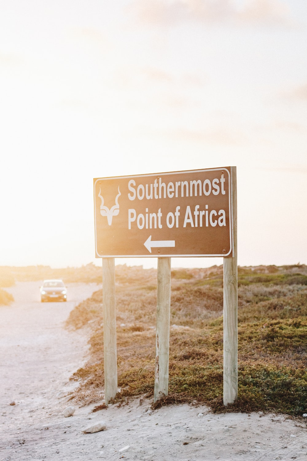 Southermost Point of Africa road sign and white vehicle on road during daytime