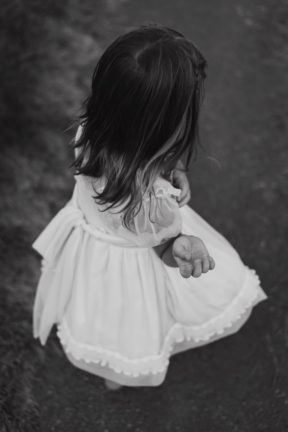 grayscale photography of child wearing dress standing while facing back