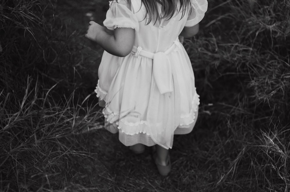 grayscale photography of girl wearing dress standing while facing back