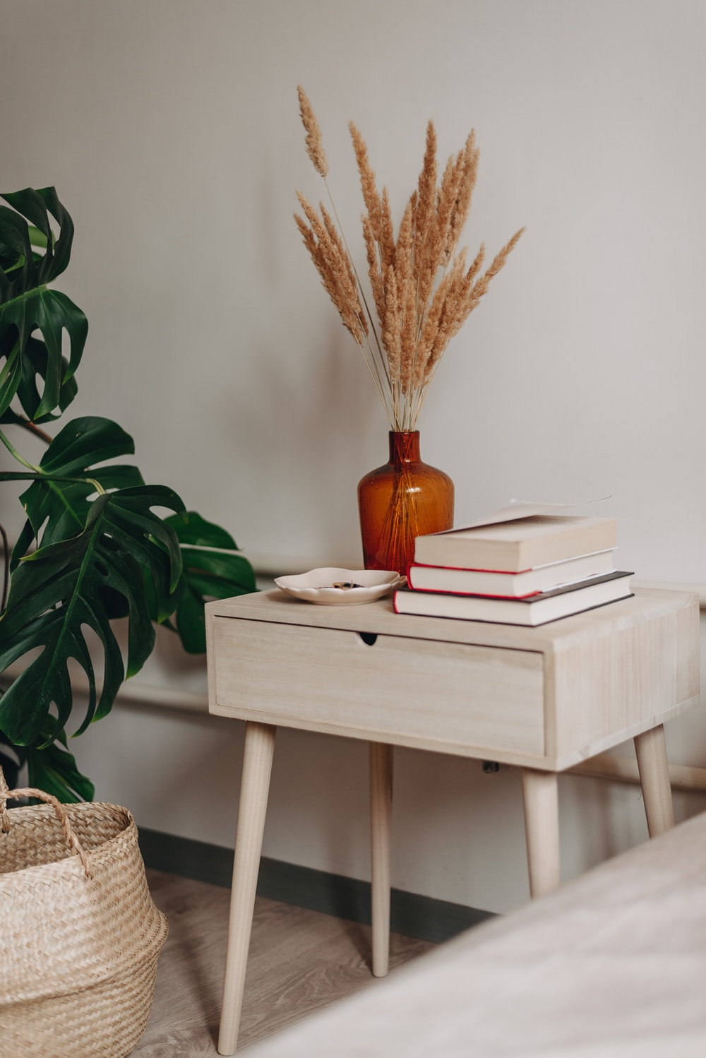 brown decorative wheat in brown ceramic vase near books on white wooden end table beside green leaf plant