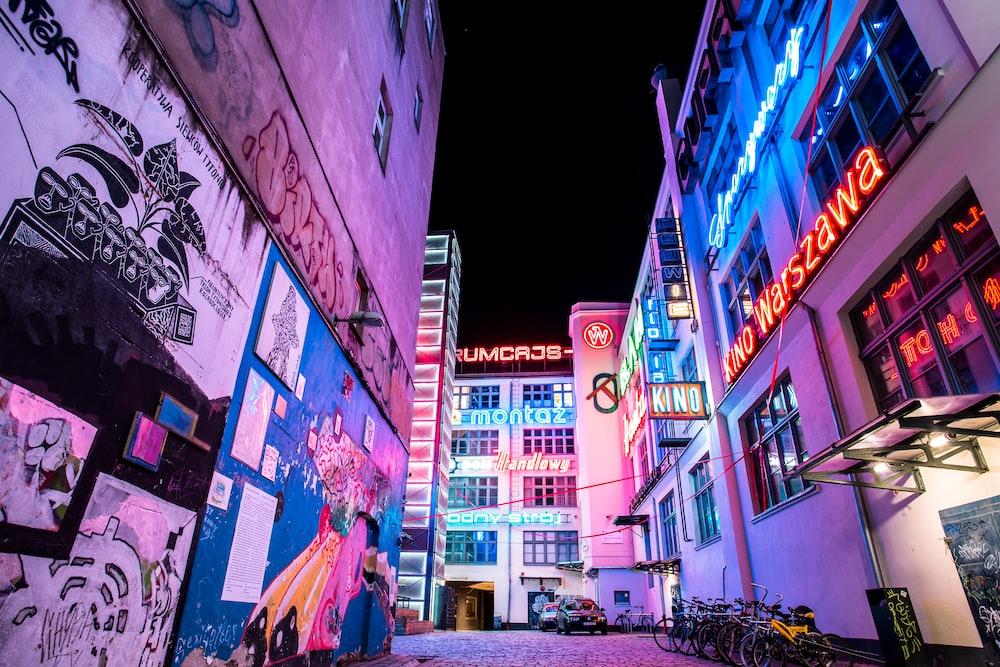 road between buildings with graffiti at night