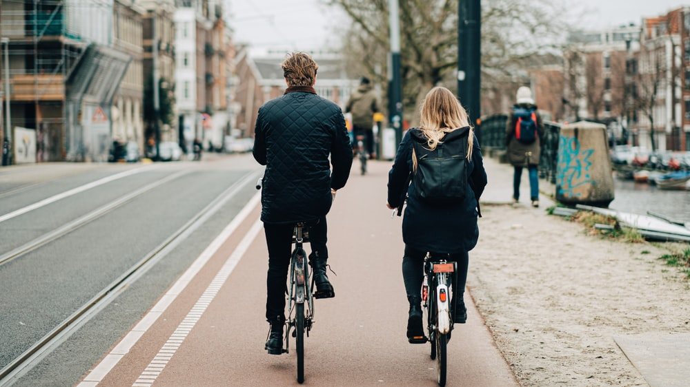 man and woman biking on road viewing buildings during daytime