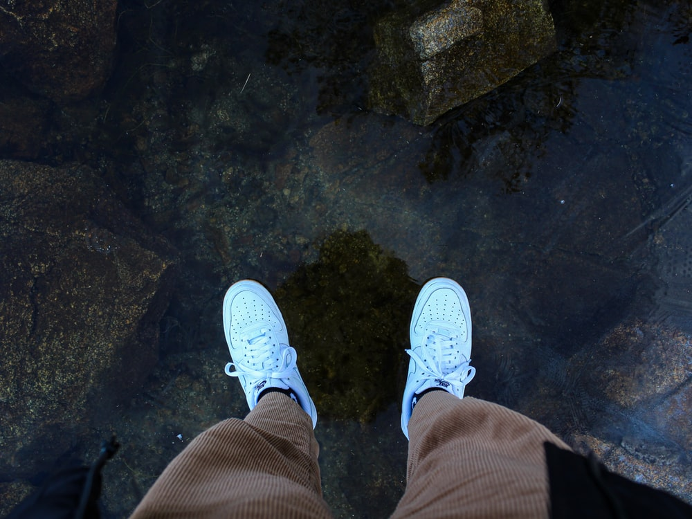 man wearing pair of white low-top sneakers