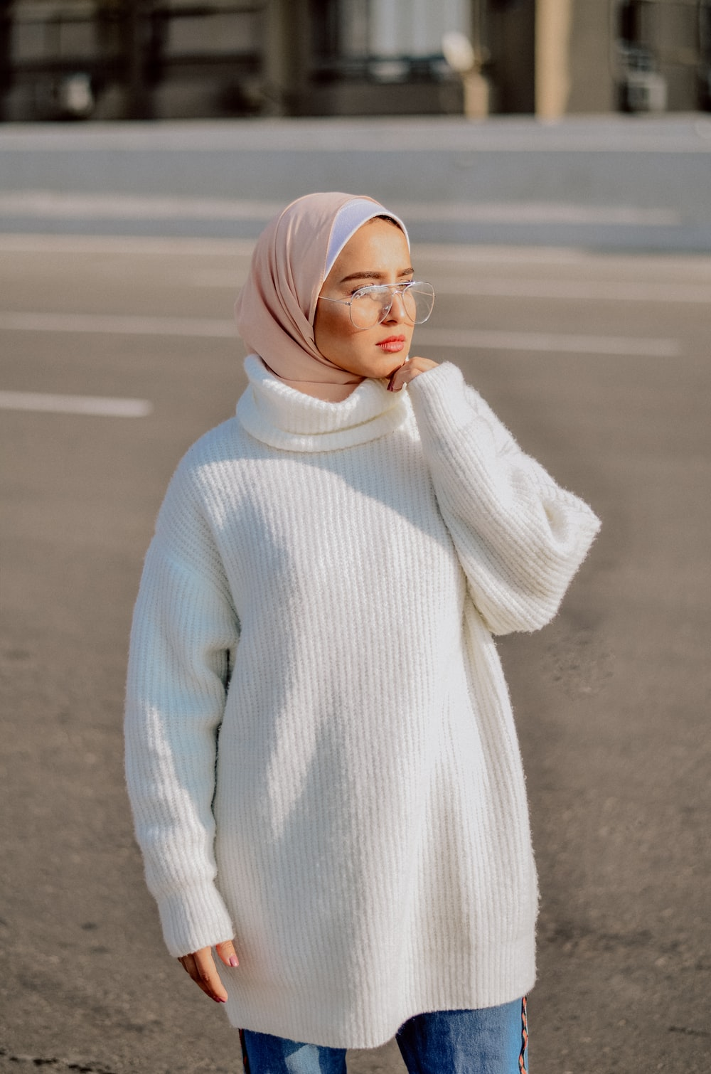 woman wearing white sweater, beige hijab headscarf, and eyeglasses standing on pathway during daytime