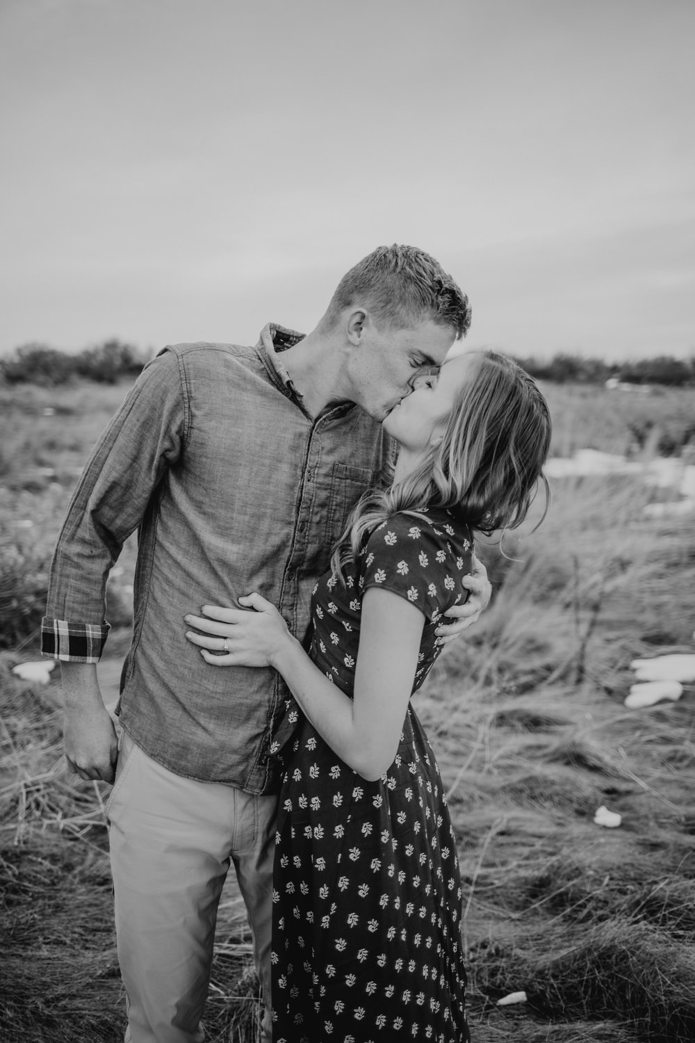 grayscale photography of man and woman standing while kissing on lips