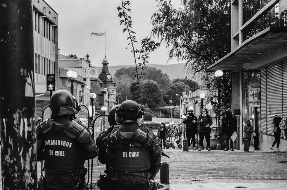 grayscale photography of police wearing armors in the street