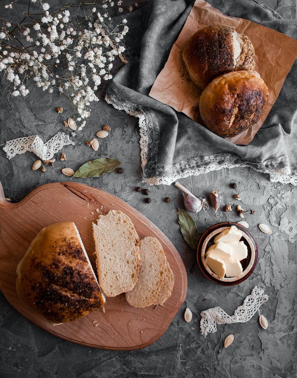 brown bread on grey textile near white flower