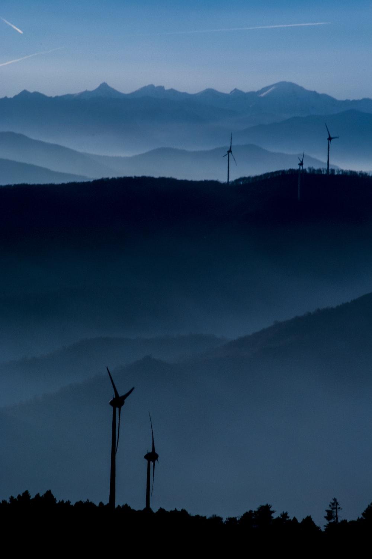 wind turbine overlooking mountain ridge