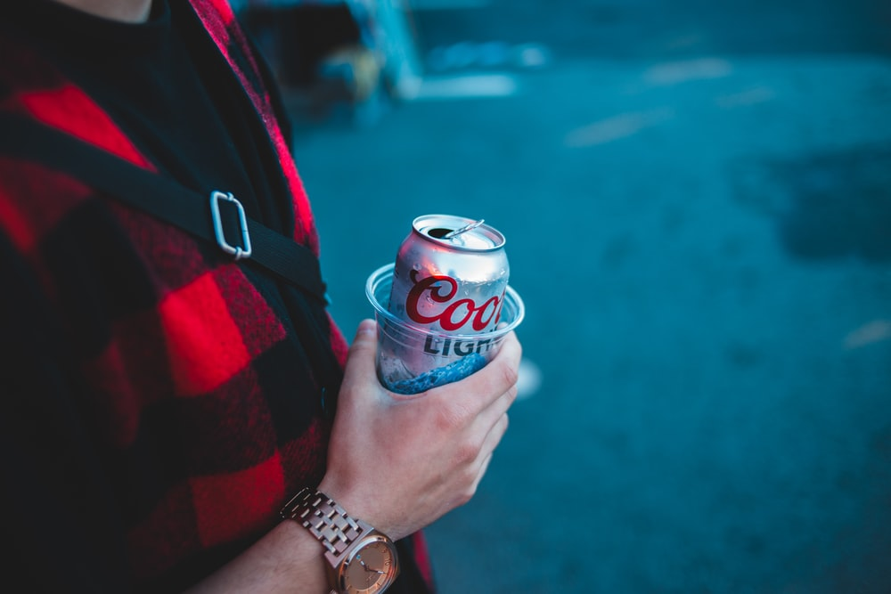 person holding Coors Light beer can