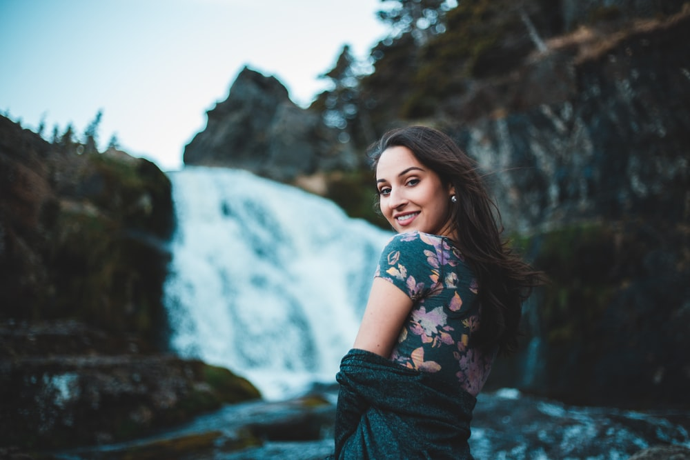 woman looking over her shoulder with waterfall in the background