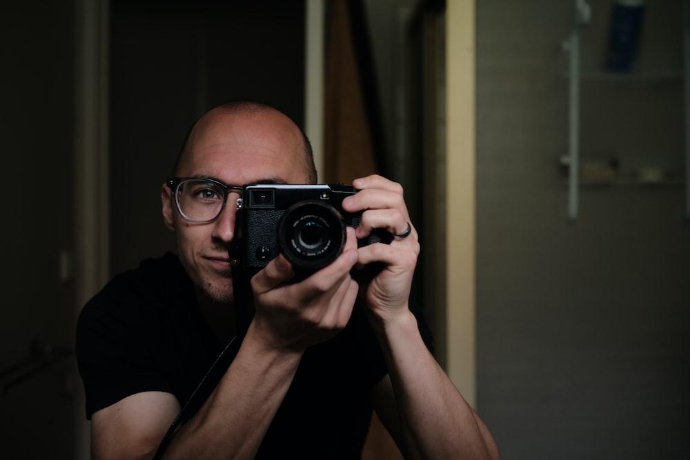 man taking picture using a black DSLR camera