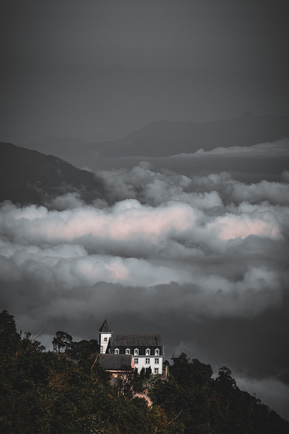 building on mountain near trees and clouds
