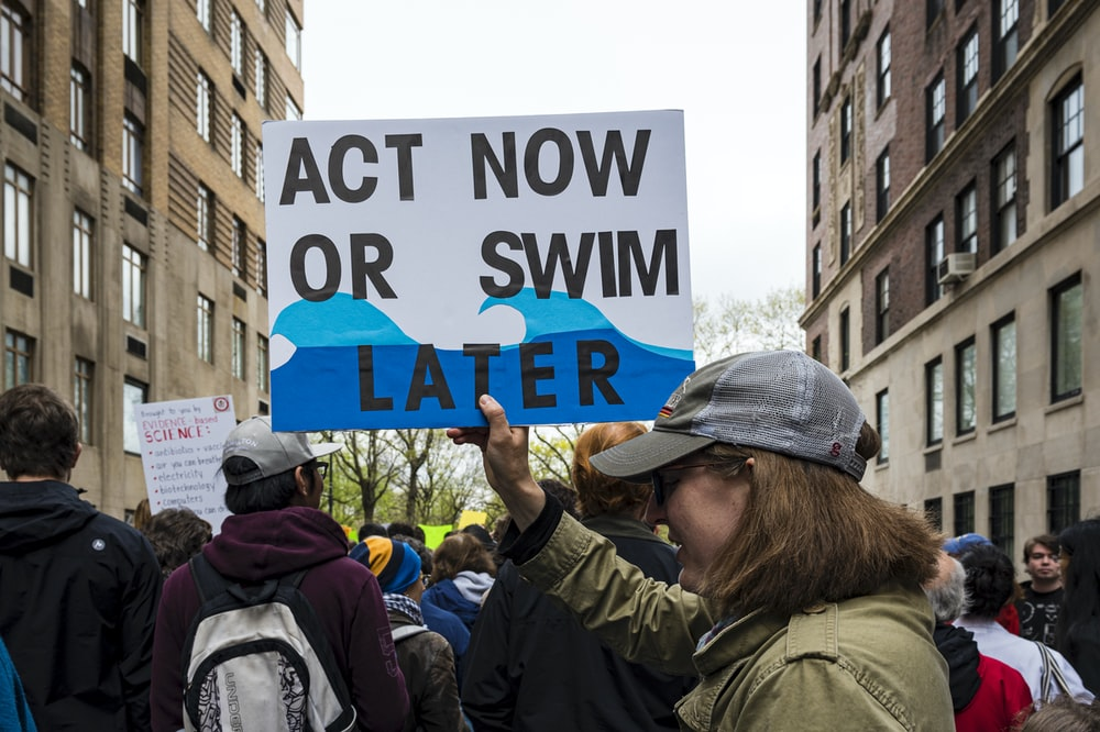 woman holding Act now or swim later signage