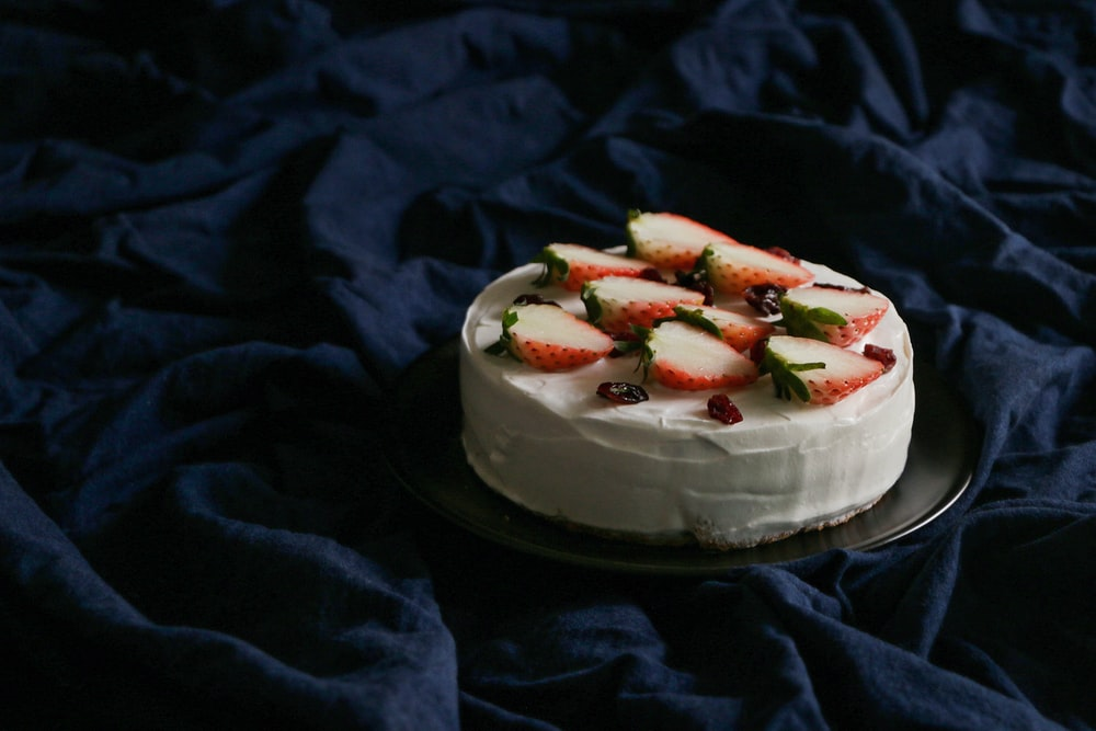 round icing cake with red strawberry toppings