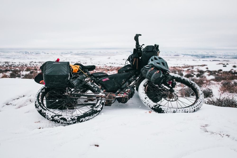 black bike on snowy road viewing body of water during daytime