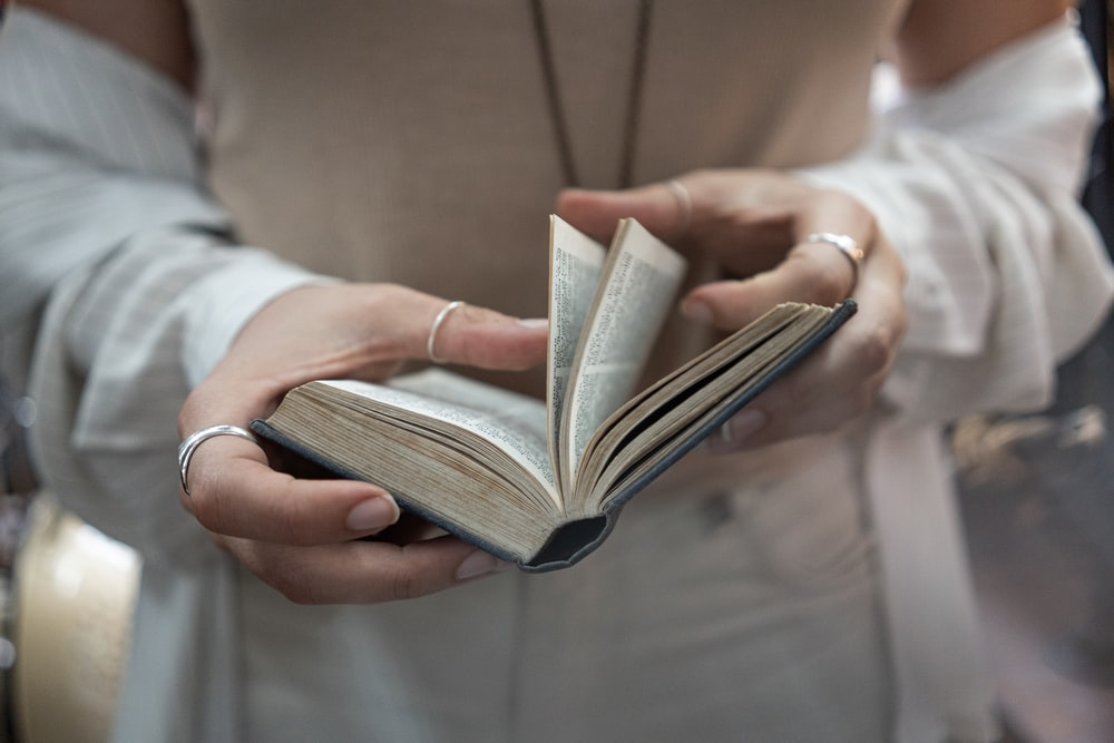woman flipping over pages of a book