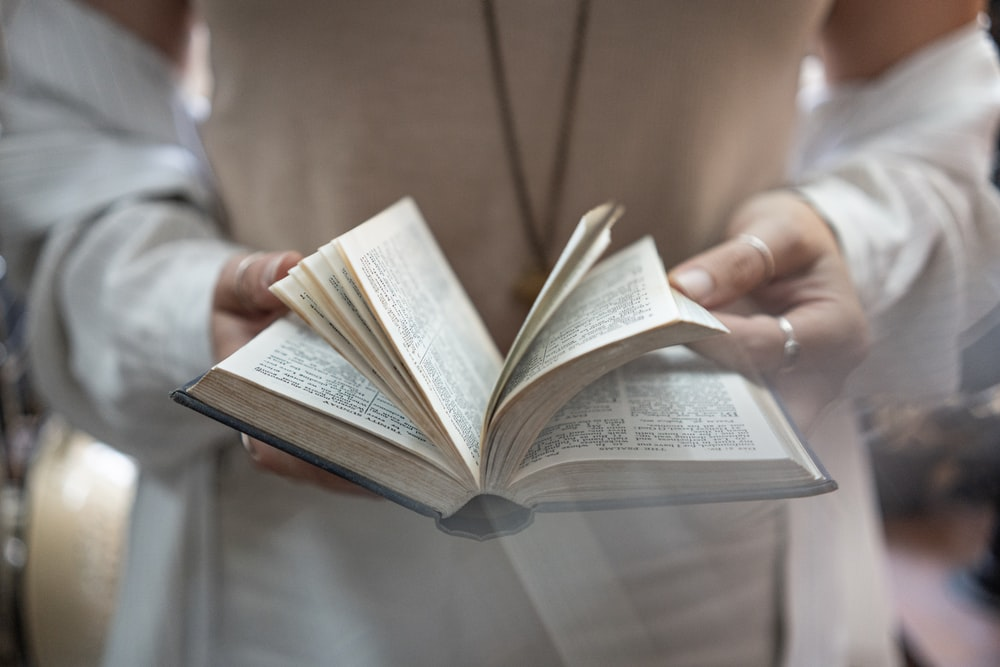 selective focus photography of person holding book