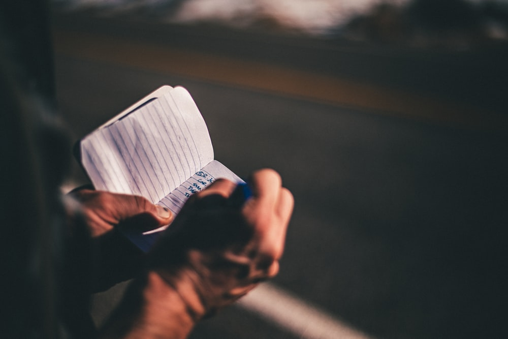 selective focus photography of person holding ruled paper