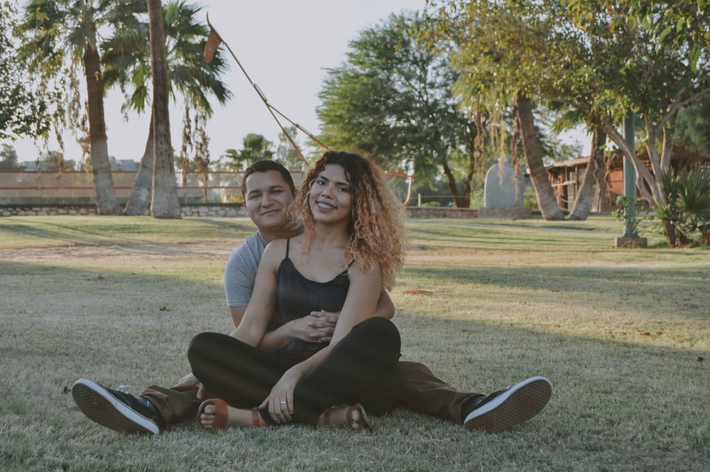 man and woman sitting on grass land